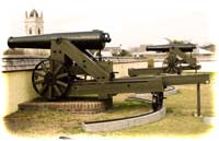 "Examples of a 32-pounder seacoast gun resting ""in battery"" at left, and another run back into its loading or recoiled position at right, in today's Fort Moultrie"