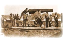 "Gunner or ""chief of piece"" demonstrating how a barbette-mounted M.1845 24-pounder was to be aimed, by sighting along its barrel while he reaches down to adjust its elevation by turning the screw-handle below its base-ring; photographed in Camp Defiance at Cairo, Illinois, June 1861"