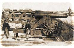 Two Union officers posing with a barbette-mounted 42-pounder seacoast gun inside of Fort Beauregard, after its capture. Immediately behind this piece is a 32-pounder, with another 42-pounder and 32-pounder visibly emplaced beyond at left. The piece with the distinctive ratcheted breech at far left, was an 8-inch Columbiad. (Library of Congress)