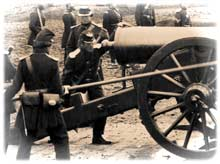 "Union gunner posed in the act of ""stopping the vent"" of a 24-pounder garrison gun at Fort Richardson, by pressing down with his finger-stall as two cannoneers thrust their sponge down its bore from the muzzle. (Library of Congress)"