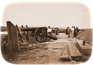 24-pounder installed on a siege-carriage at Camp Defiance, with another atop a barbette-carriage further behind, and a small 8-inch siege mortar in between both, ca. June 1861. The epaulement on the Ohio River embankment at left is still being raised, while the edge of the battery's mounded magazine can be glimpsed at far right. (Library of Congress)