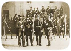 Officers of the Charleston Zouave Cadets posing around their Capt. Charles E. Chichester, outside the main gate of Castle Pinckney in late 1861, still wearing their blue militia-issue uniforms, plus forage caps
