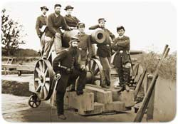 Group of soldiers posing for a photo atop a 24pounder cannon